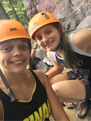 two campers with climbing helmets and harnesses